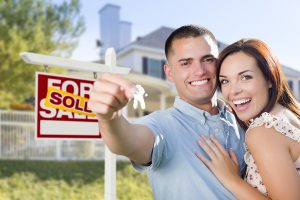 Couple In Front of New Home with For Sale sign holding keys