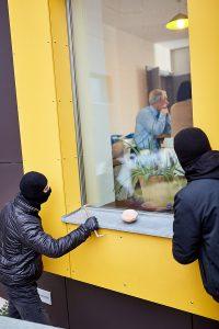 two burglars peaking into window