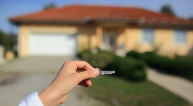 Hand displaying keys in front of a new home