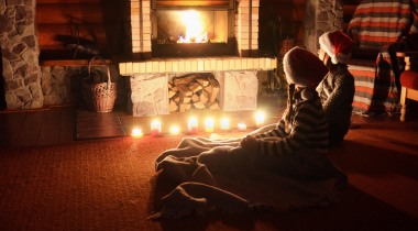 Children sitting around a fireplace with candles